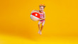 funny happy child  jumping in swimsuit    on colored background