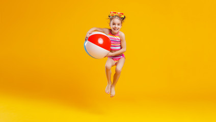 funny happy child  jumping in swimsuit    on colored background © JenkoAtaman