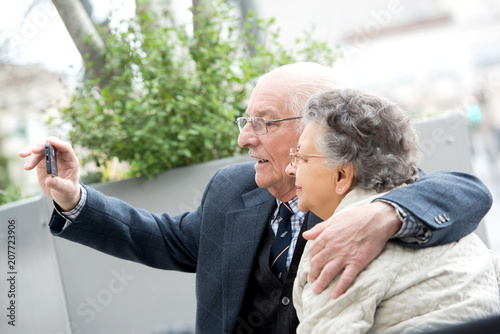 Sticker senior couple with camera taking selfie on street