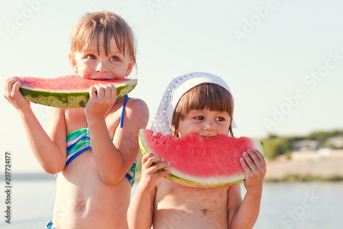 Leinwanddruck Bild Little girls eat watermelon on the beach