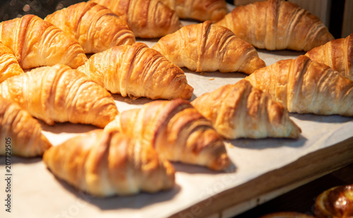 Foto Murales Croissants in a bakery shop. freshly baked croissants on texture background.