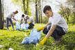 Save nature. Happy male volunteer using garbage bag while gathering litter
