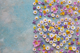 Background with flowers of daisies, lilacs, forget-me-nots, roses, pansies, buttercups, petals and heart