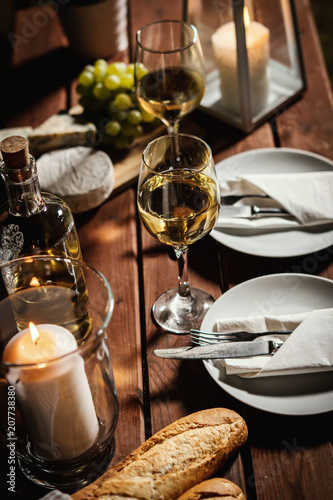 romantic dinner with two glasses of wine, a baguette and snacks on an old wooden table on a summer evening - 207738380