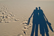 Shadows of pair of tourists on sand dunes
