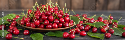 Tasty juicy sweet cherry on a wooden background. It can be used as a background - 207746312