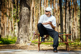 man in a white hat with a skateboard sits on a picnic table and uses a phone in a summer park - 207748396