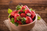 strawberries in wooden bowl on wood table