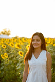 Young happy Asian woman smiling and thinking in the field of blo