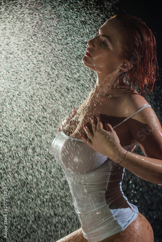 Fotobehang Kapsalon A beautiful woman with short red hair, big Breasts, short transparent, wet, white shirt, very sexy posing under the drops and jets of water. Dark background