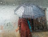 Monsoon season in Kathmandu, Nepal. Woman holding an umbrella seen through a window. Focus on droplets on glass. - 207754737