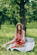 pretty young woman in hat resting on blanket with wicker basket with apples in park