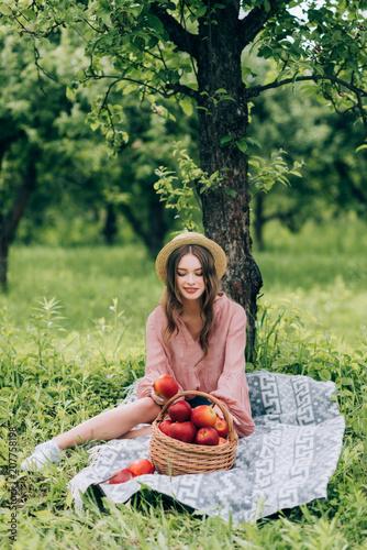 ładna młoda kobieta w kapeluszu odpoczywa na koc z łozinowym koszem z jabłkami w parku