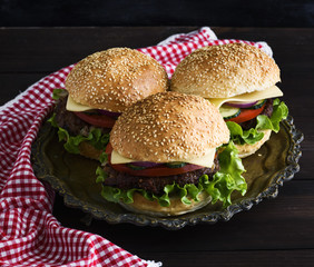 three burgers with a meat chop, vegetables and cheese