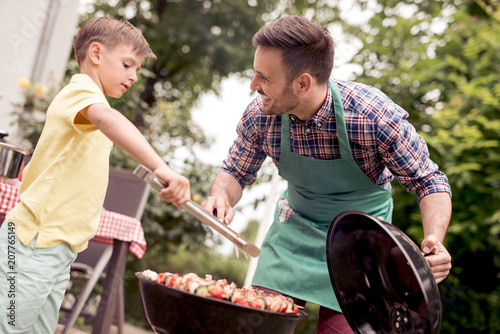 Dad and son having a barbecue party