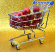 shopping cart with red decorative Christmas balls and golden bac