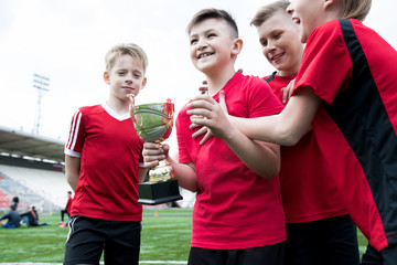 Portrait of junior football team holding trophy together and cheering happily after winning match in outdoor stadium