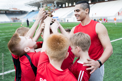 Portrait of junior football team holding trophy together and cheering after winning match in outdoor stadium