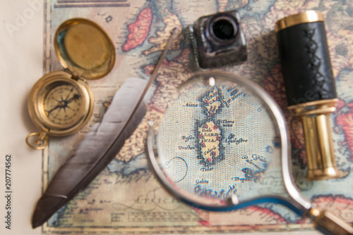 Foto Murales Closeup view of a magnifying glass on an old map with vintage items