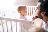 A small toddler girl standing in cot with her father at home. - 207776756