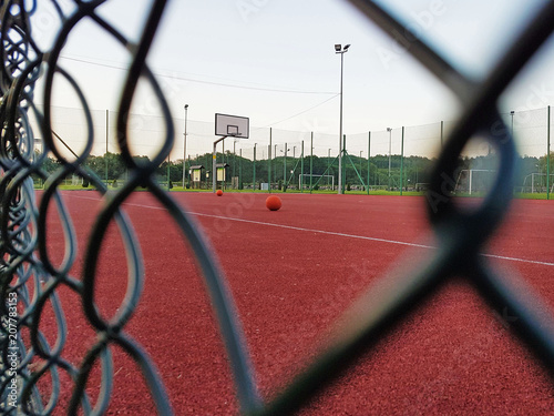 Fotobehang Tennis Modern basketball court under the open sky with artificial red coating. Location of team sports events. Physical education of citizens. Healthy lifestyle. Urban infrastructure for recreation, interest