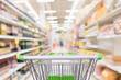 Leinwanddruck Bild - Empty green shopping cart with abstract blur supermarket discount store aisle and seasoning sauce product bottle shelves interior defocused background