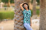 portrait of a brunette girl in sunglasses near a palm tree