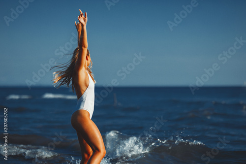 Young woman posing on the beach in a white swimsuit