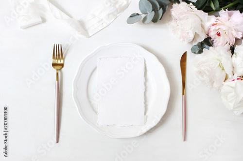 Foto Murales Feminine wedding, birthday desktop mock-up scene. Porcelain plate, blank craft paper greeting cards, silk ribbon, golden cutlery, eucalyptus, peony flowers. White table background. Flat lay, top view