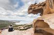 Frau sitzt alleine auf dem Bärenfelsen Roccia dell'Orso und genießt die Aussicht über das Mittelmeer auf Sardinien