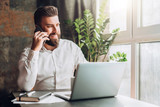 Young smiling bearded businessman is sitting at table in front of laptop, drinking coffee, talking on cell phone. Telephone conversations, distance work, online marketing, education, e-commerce. - 207818166