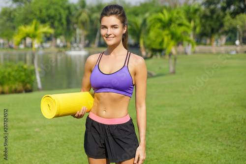 Fotobehang School de yoga Woman with a fitness mat in the park