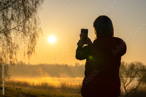 Fotobehang Oranje Tourist woman taking a photo with smartphone on sunset nature background
