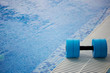 The kettlebell for water aerobics lies on the edge of the pool. Near the water. Exercise, swimming and a healthy lifestyle