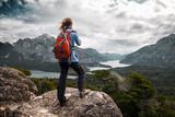 Tourist hiker with red backpack takes pictures of the valley with mountains and lakes. Patagonia, Argentina - 207829783