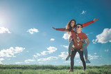 I believe we can fly. Full length of amorous couple looking at blue sky. Girl is on her boyfriend back with stretched arms. They smiling and enjoying summer weather. Copy space in left side - 207831336