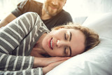 Portrait of tranquil smiling woman sleeping on white pillow. Caring partner is lying behind and looking at her with love - 207832726