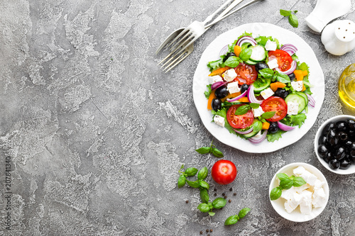 Grecka sałatka. Sałatka ze świeżych warzyw z pomidorami, cebulą, ogórkami, bazylią, papryką, oliwkami, sałatą i serem feta. Grecka sałatka na talerzu