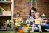 Mom and children are planting flowers - 207870339