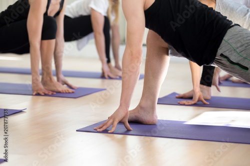 Group of young sporty people practicing yoga lesson, doing Utthan Pristhasana exercise, Lizard pose, working out, indoor close up, students training in sport club. Wellness, wellbeing concept