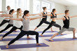 Leinwanddruck Bild - Group of young sporty people practicing yoga, doing Warrior II exercise, Virabhadrasana 2 pose, indoor full length, yogi students working out in sport club, studio. Active lifestyle, wellness concept