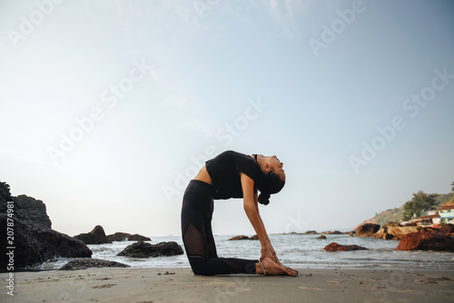 Fotobehang School de yoga Young healthy woman practicing yoga on the beach at sunset