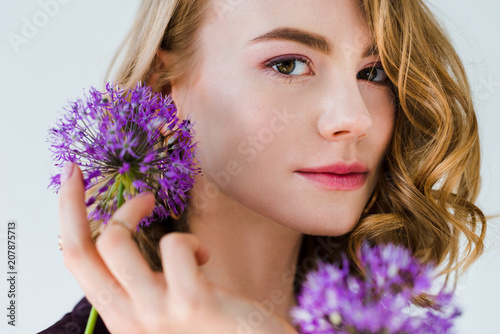 Foto Murales beautiful girl holding fresh violet flowers and looking at camera isolated on grey