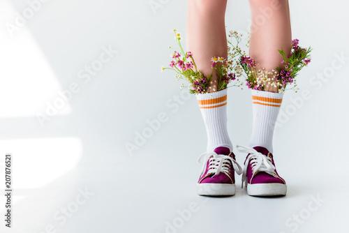 Leinwanddruck Bild cropped shot of girl with fresh flowers in socks on grey