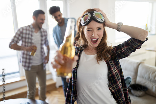 Small group of young people hang out at the house party, friends having fun