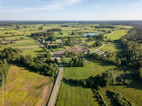 Canvas Honing drone image. asphalt road surrounded by pine forest and fields from above