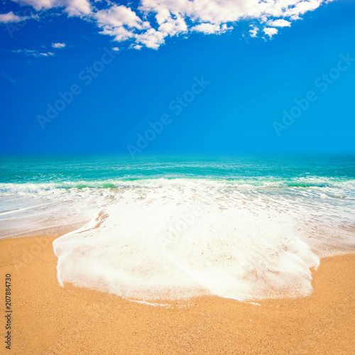 Beautiful beach with Soft waves of blue ocean on sandy beach. Tropical paradise. Travel tourism background concept.