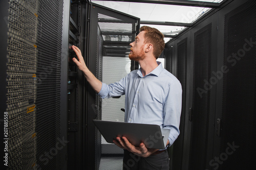 Confident IT Technician Examining Server Closet While Carrying Laptop