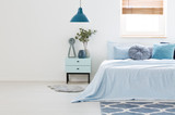 Real photo of a blue and white bedroom interior with wooden nightstand between a light blue bed and an empty wall. Paste your armchair here - 207885997