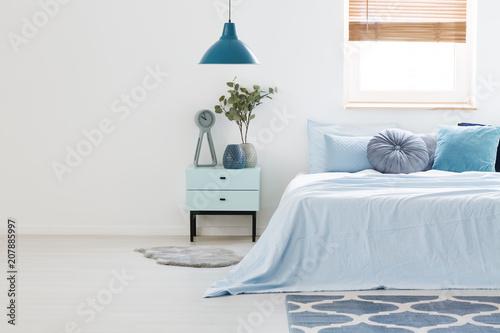 Prawdziwe zdjęcie niebieskiego i białego wnętrza sypialni z drewnianym stolikiem nocnym między jasnoniebieskim łóżkiem i pustą ścianą. Wklej tutaj swój fotel